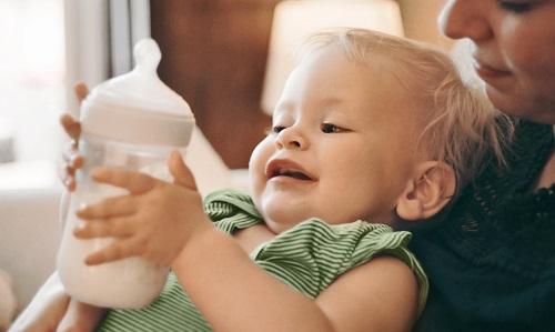 אם מחזיקה תינוק בידיה כאשר הוא מחזיק בידיו בקבוק הזנה